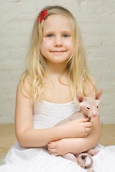 子猫のスフィンクスと若い笑顔の女の子