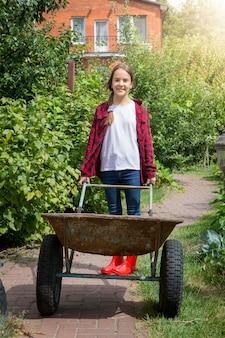Молодая улыбающаяся девушка с тачкой, работающая в саду в солнечный день