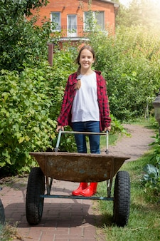 Young smiling girl with wheelbarrow working at garden at sunny day
