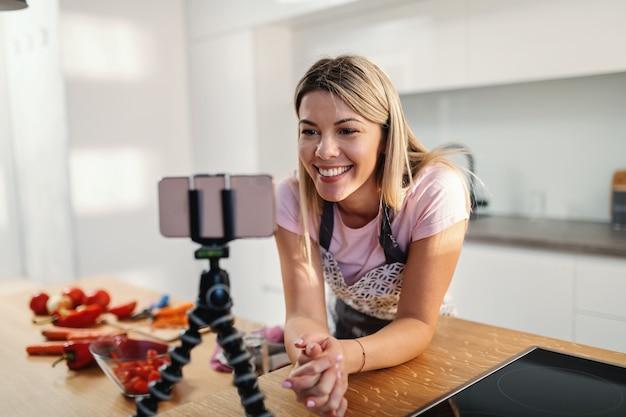 台所のテーブルに寄りかかって三脚でスマートフォンを見ている若い笑顔のゴージャスな金髪の主婦。彼女はヘルシーなランチのレシピを探しています。
