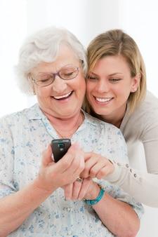 Молодая улыбающаяся внучка показывает и обучает свою бабушку мобильному телефону