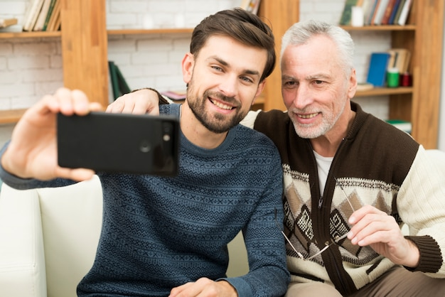 Young smiling guy and aged cheerful man taking selfie on smartphone on settee