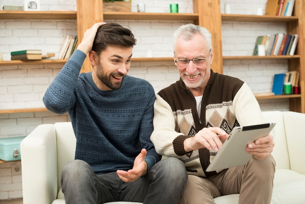 Young smiling guy and aged cheerful man using tablet on settee