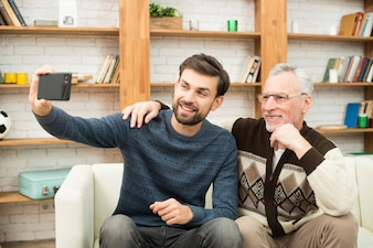 Young smiling guy and aged man taking selfie on smartphone on sofa