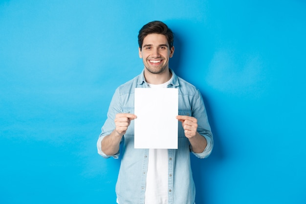 Young smiling guy in casual outfit, holding blank piece of paper with your advertisement, standing over blue background.