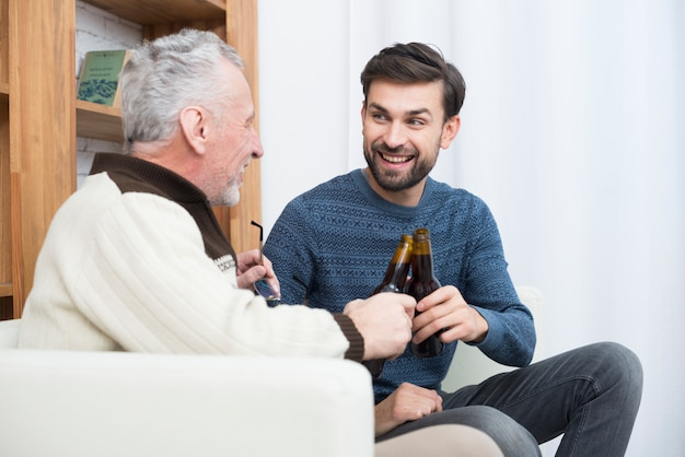 Young smiling guy clanging bottles with aged man on sofa