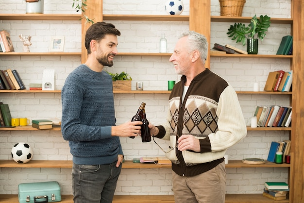 Young smiling guy clanging bottles with aged man
