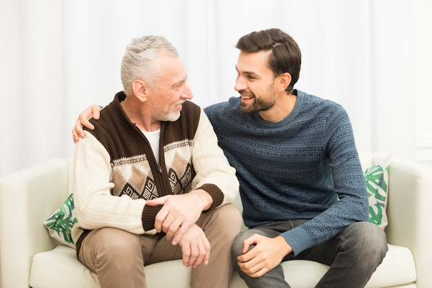 Young smiling guy hugging aged man on sofa