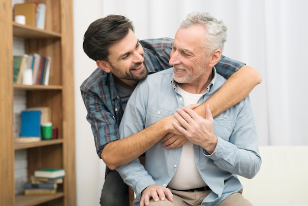 Young smiling guy hugging aged man