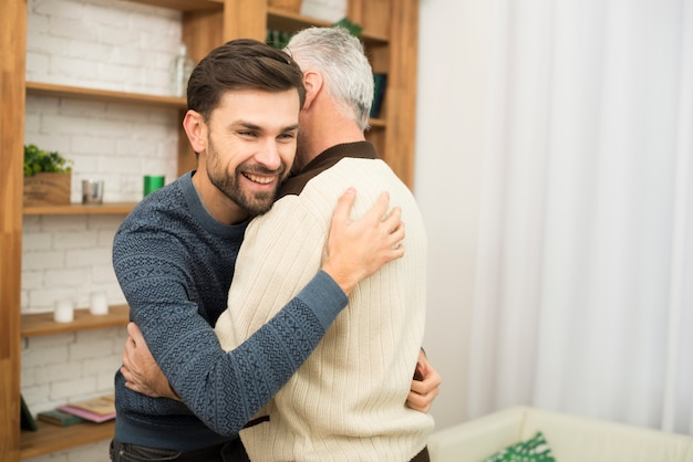 Young smiling guy hugging with aged man near bookshelves