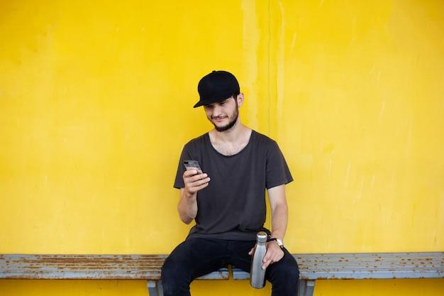 젊은 웃는 남자가 손에 강철 병으로 노란색 뒤에 앉아 스마트 폰에서 찾고 있습니다.