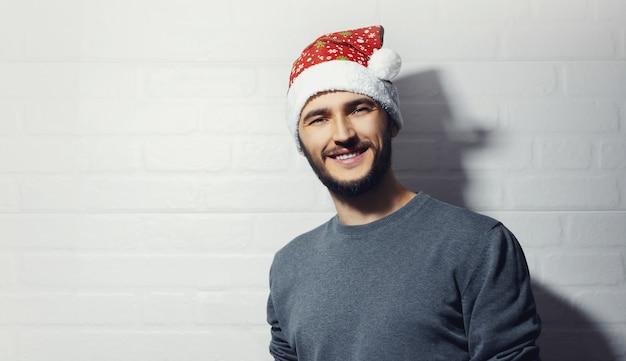 白いレンガの壁の背景に若い笑顔の男。クリスマスのコンセプト。