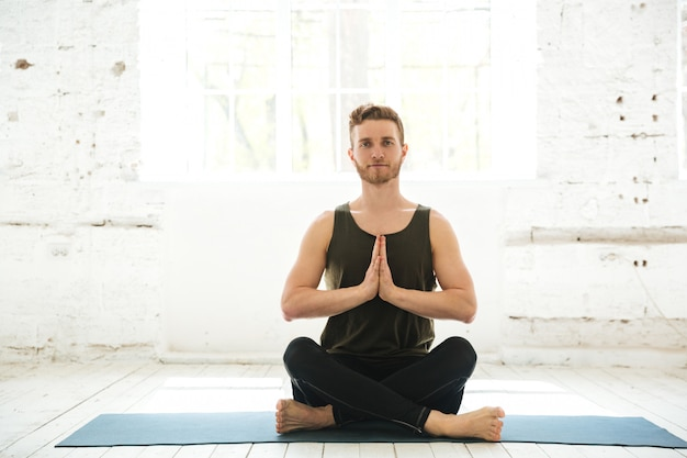 Young smiling guy sitting on a fitness mat and meditating