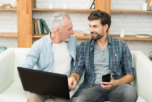 Young smiling guy with smartphone pointing at monitor of laptop on legs of aged man on sofa