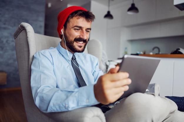 Молодой улыбающийся красивый бородатый отец одет в деловой случайный, сидя в кресле и с помощью планшета для работы.