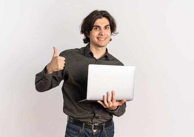 Il giovane uomo caucasico bello sorridente tiene il computer portatile e il pollice in alto isolato su priorità bassa bianca con lo spazio della copia
