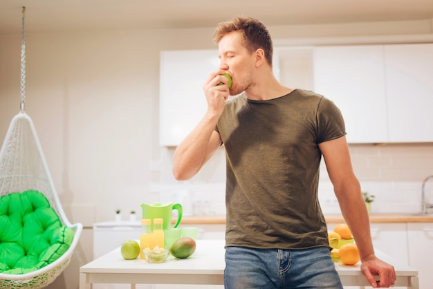 Young smiling handsome man bites organic apple while cooking fresh fruits in the kitchen.