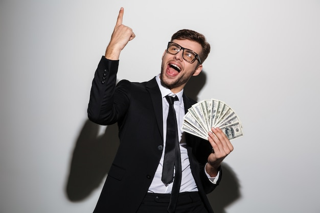 Young smiling handsome man in classic black suit holding bunch of money while pointing with finger upward