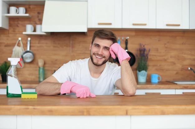 웃고 있는 젊고 잘생긴 남자는 부엌을 청소할 필요가 있다고 생각합니다.