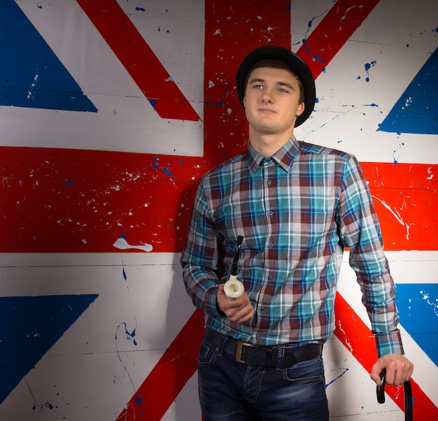 Young smiling handsome man with smoking pipe and cane in trendy fashion outfit in front britain flag
