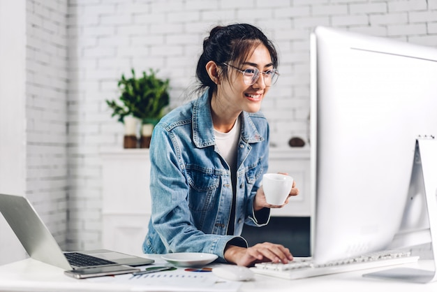 Young smiling happy asian woman relaxing using desktop computer working and video conference meeting online chat.young creative girl drink coffee at home.work from home concept