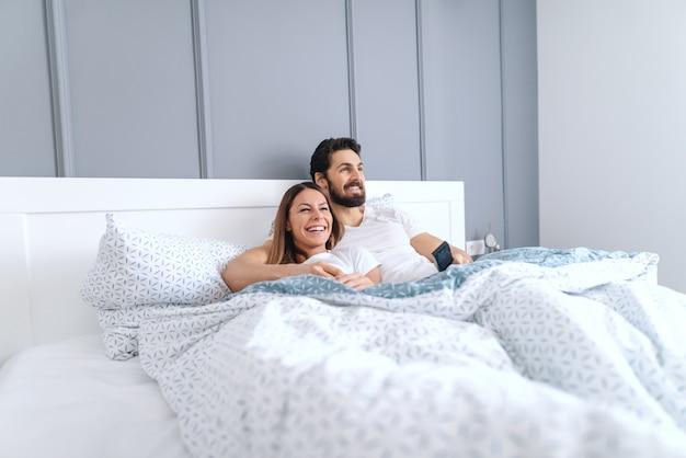 Молодые улыбающиеся счастливые привлекательные кавказские пары, лежа в постели и смотреть телевизор по утрам. интерьер спальни.