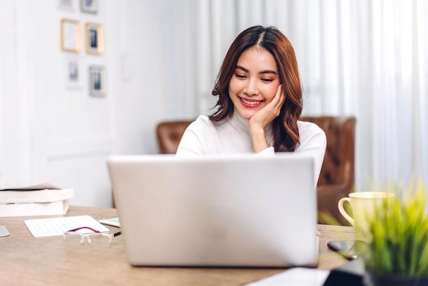Молодая улыбающаяся счастливая красивая азиатская женщина расслабляется с помощью портативного компьютера в комнате дома. молодая творческая девушка работает и печатает на клавиатуре. работа из дома концепции