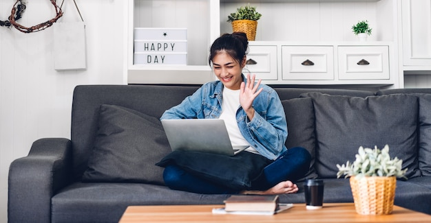 Женщина детенышей усмехаясь счастливая красивая азиатская ослабляя используя работу портативного компьютера и встречу видеоконференции дома. молодая творческая девушка сказать привет и набрав на клавиатуре. работать из дома концепции