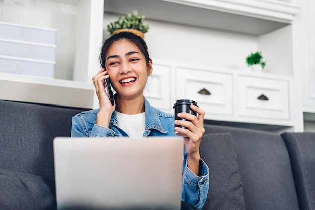 Женщина детенышей усмехаясь счастливая красивая азиатская ослабляя используя работу портативного компьютера и встречу видеоконференции дома. молодая творческая девушка разговаривает с smartphone и выпивает кофе. работать из дома концепции