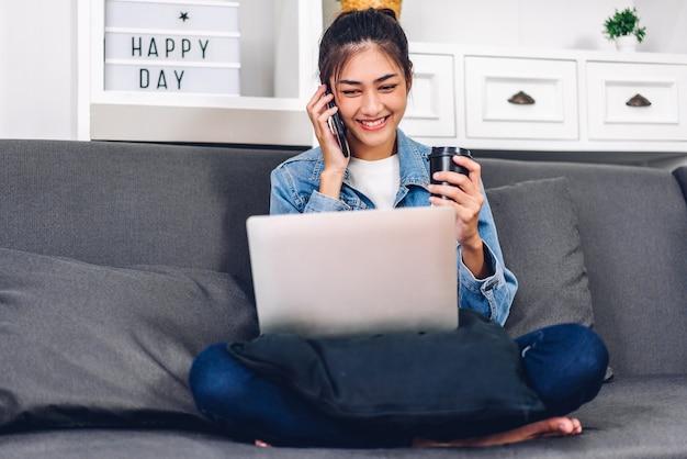Молодая усмехаясь счастливая красивая азиатская женщина ослабляя используя работу портативного компьютера и встречу по видеоконференции дома.