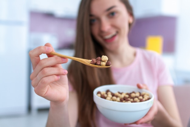 Young, smiling happy beautiful brunette woman holding cereals spoon and cereals bowl full of chocolate balls for breakfast at home