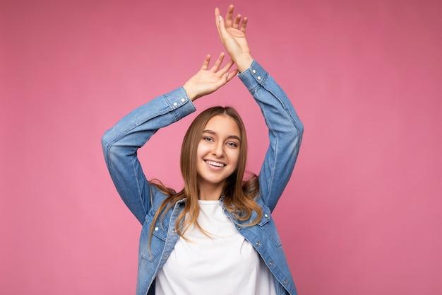 モックアップとデニムシャツのカジュアルな白いtシャツを着てコピースペースと背景の壁に分離された誠実な感情を持つ若い笑顔の幸せな美しいダークブロンドの女性。ポジティブなコンセプト。