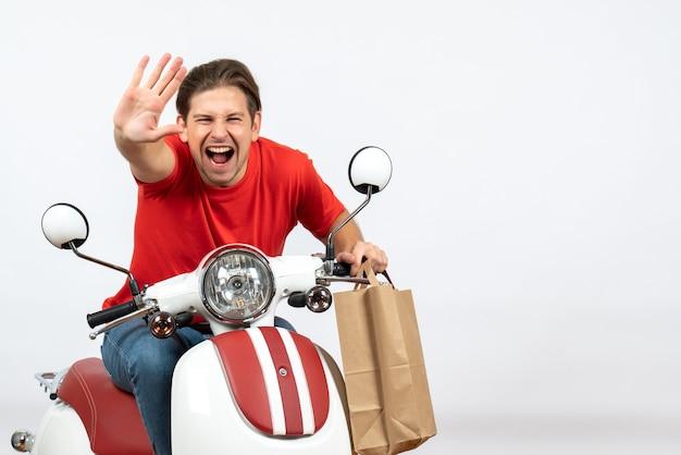 黄色の壁に5を示す注文を保持しているスクーターに座っている赤い制服を着た若い笑顔の幸せな宅配便の男