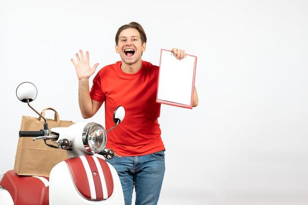 白い壁に5を示す文書を保持しているスクーターの近くに立っている赤い制服を着た若い笑顔の幸せな配達人