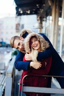 Молодая улыбающаяся счастливая европейская пара, обнимающая зимой
