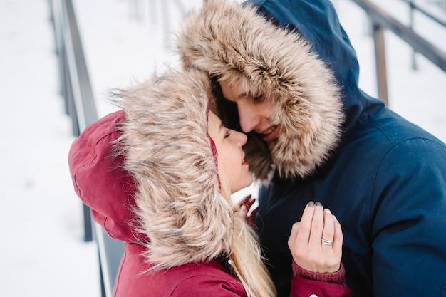 冬に抱いて幸せなヨーロッパのカップルの笑顔若い