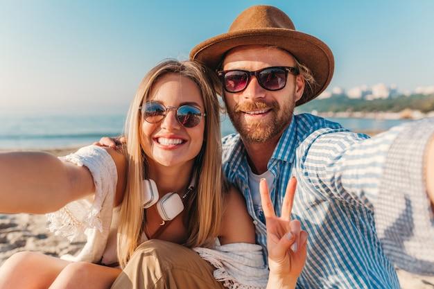 Молодой улыбающийся счастливый мужчина и женщина в солнцезащитных очках, сидя на песчаном пляже, принимая селфи-фото на камеру телефона