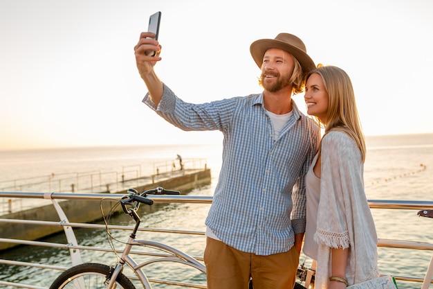 Молодой улыбающийся счастливый мужчина и женщина, путешествующие на велосипедах, делающие селфи на камеру телефона