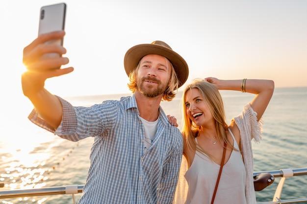 若い笑顔幸せな男と携帯電話のカメラでselfie写真を撮る自転車で旅行する女性