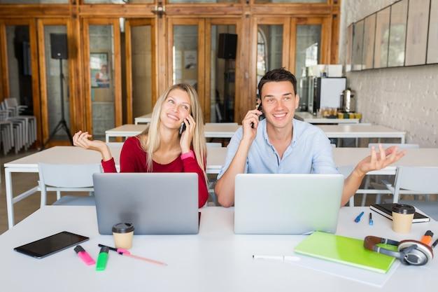 若い笑顔幸せな男とオープンスペースの共同作業事務室でラップトップに取り組んでいる女性