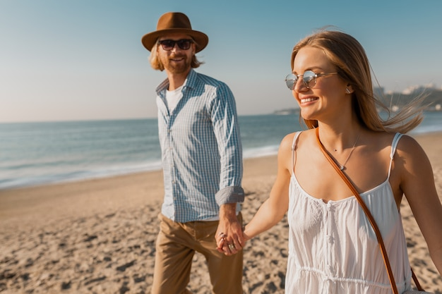Young smiling happy man in hat and blond woman running together on beach on summer vacation traveling