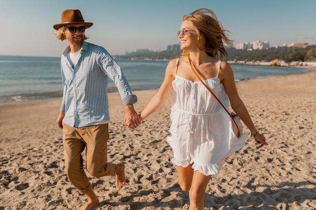 Young smiling happy man in hat and blond woman in white dress running together on beach on summer vacation traveling