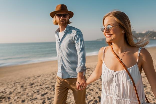 夏休み旅行のビーチで一緒に走っている帽子と金髪の女性の若い笑顔幸せな男