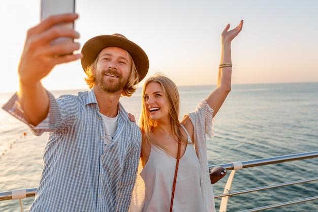 Giovane sorridente felice uomo e donna che viaggiano in bicicletta prendendo selfie foto sulla fotocamera del telefono