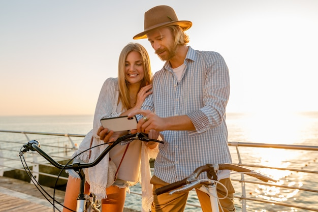 Young smiling happy man and woman traveling on bicycles taking selfie photo on phone camera