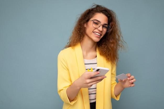 カメラを見てクレジットカードを介してオンラインショッピングを支払う電話とクレジットカードを保持している背景に隔離された日常服を着て若い笑顔の幸せな女性。