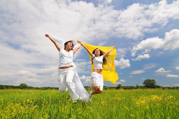 晴れた日の夏に牧草地と緑の草で上げられた手でジャンプしてシルクのショールを持って白い服を着た若い笑顔の幸せな女性。メンタルヘルスとポジティブエネルギーの概念