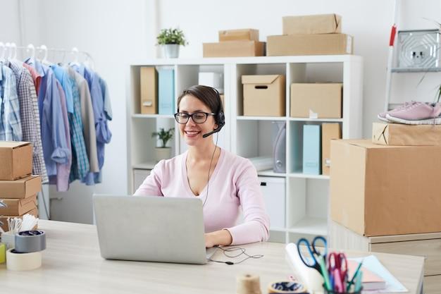 Молодой улыбающийся менеджер службы поддержки разговаривает с клиентами онлайн