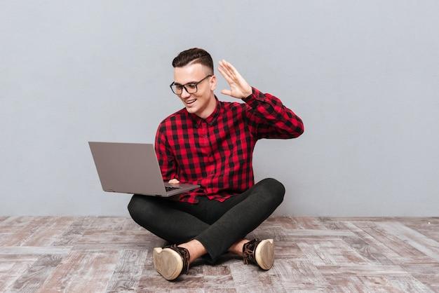 Молодой улыбающийся битник в очках, сидя на деревянном полу с ноутбуком и размахивая в камеру ноутбука. изолированный серый фон