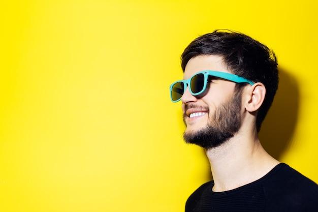 Молодой улыбающийся хипстер с солнечными очками цвета морской волны на оранжевой стене.